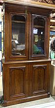 American Victorian style breakfront display cabinet, executed in walnut, having a molded top above two glass paneled doors accented ...