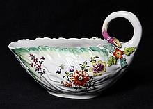 Early Derby sauce boat, 18th century, having a naturalistic twig handle with applied flowers and leaves on a body with a shaped rim...