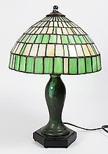 (lot of 2) Arts & Crafts mosaic glass table lamp, having a green and cream tile pattern, rising on a vasiform ceramic standard glaze...