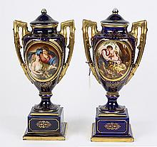 Pair of Royal Vienna enamel decorated covered urns, each having a cobalt blue body with gilt and enamel reserves flanking the centra...