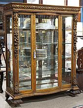 American Victorian golden oak vitrine circa 1880, having a molded and carved crest flanked with acanthus and floral carved mounts, c...