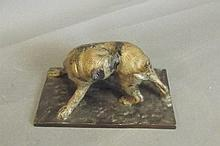 A cold painted bronze statue of a dog biting a