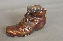 A cold painted bronze rat climbing on an old boot,