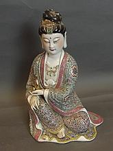 A Chinese pottery Buddha with polychrome enamel