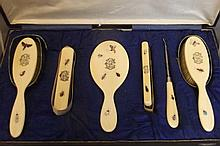 A cased ivory dressing table set consisting of