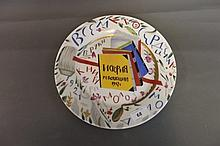 A Russian pottery plate painted with books and a