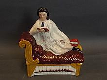 A Staffordshire seated figure of a musician with