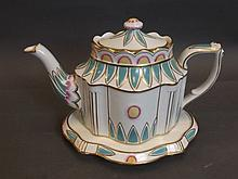 A shaped English teapot on raised shaped stand