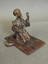 A patinated bronze model of a praying Arabian man,
