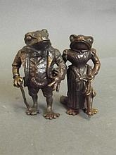 A bronze model of two anthropomorphic frogs,