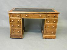 A Victorian oak 9 drawer pedestal desk with a