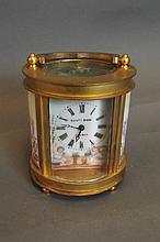 An oval shaped brass carriage clock with