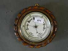 An early C20th wall barometer on a carved oak
