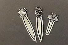 Three silver bookmarks in the form of two flowers