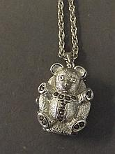 A watch pendant in the form of a teddy bear, on a