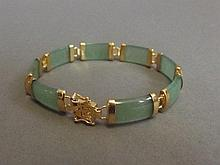 A Chinese yellow metal and apple jade bracelet,