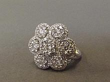 An 18ct white gold seven diamond cluster flower