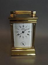 A brass carriage clock with alarm in working
