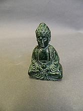 A Chinese green hardstone pendant carved in the