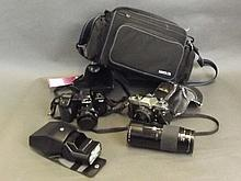 Two Minolta 35mm film cameras with accessories and