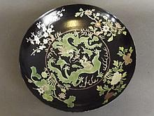 A Chinese famille noir dish painted with green dra
