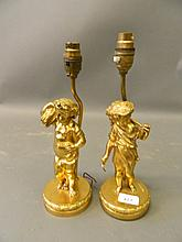 A pair of gilt bronze lamps in the form of cherub