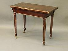 An Edwardian mahogany fold over card table on squa