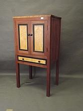 A small contemporary hardwood press cupboard with