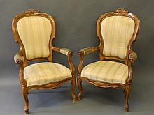 A pair of carved maple open armchairs with shaped