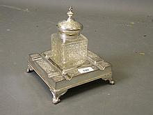 A cut glass inkwell with silver plated mounts on a