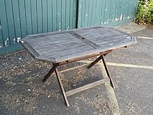 A teak fold-up garden table, 59'' x 31''