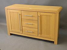 An oak veneered buffet with two cupboards flanking