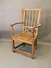 A late C19th oak commode chair with shaped arms an