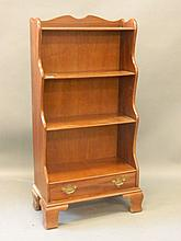 A mahogany four shelf waterfall bookcase with sing