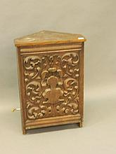 A standing oak corner cabinet with a decoratively