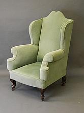 A Georgian style wing back armchair on cabriole su