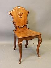 A Victorian mahogany hall chair with carved shaped