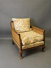 A 1930s walnut framed bergere chair with double ca