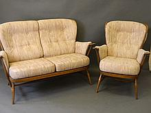 An Ercol stained beech two seater settee with matc