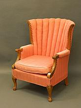 A tub shaped elbow chair with shaped back on cabri