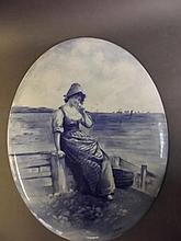 A Doulton Burslem blue and white oval plaque depicting a Dutch girl sitting