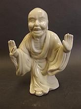 A Chinese cream glazed porcelain figure of Buddha, seal mark to back, 6
