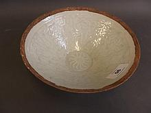 A Chinese Sung style porcelain bowl with celadon glaze and embossed decorat