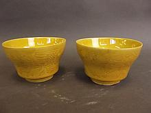 A pair of Chinese porcelain yellow glazed bowls with incised decoration of