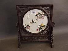 A Chinese table screen with central porcelain panel decorated with birds, blossoms and calligraphy, in an ornately pierced and carved hardwood frame, 13½