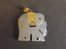 A Chinese white jade and gold pendant carved as an elephant