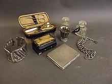 A silver bangle, compact, small cup, and a manicure set (cup AF)