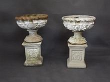 A pair of painted reconstituted stone urns on pedestal bases with raised cl