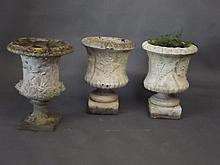 A pair of reconstituted stone urns with fern decoration, and another with c