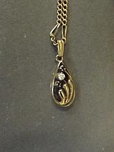 A 10ct gold pendant on chain set with a diamond